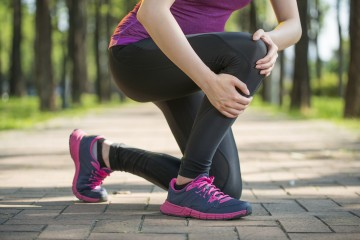 Sportlerin hält sich Knie das schmerzt.